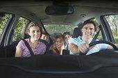 stock photo of seatbelt  - Portrait of smiling couple with three children in car - JPG