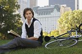 Portrait of handsome young businessman reading book by bicycle in park