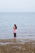 Rear view of young woman standing by seaside on beach