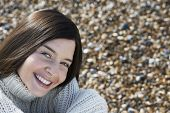 stock photo of herne bay beach  - Portrait of happy young woman smiling while sitting at beach - JPG