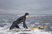 Profile shot of young man in wetsuit surfing at beach