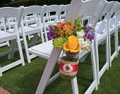 picture of lawn chair  - Rows of white chairs set up for a wedding with vase of flowers on the end - JPG