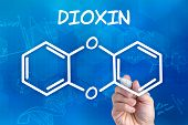 hand with pen drawing the chemical formula of dioxin