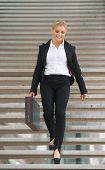 Confident Business Woman Walking Downstairs With Briefcase