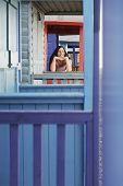 stock photo of herne bay beach  - Beautiful young woman looking away while leaning on balustrade of beach house - JPG