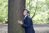 Businessman with eyes closed embracing tree trunk in forest