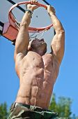foto of nipple rings  - Handsome muscular bodybuilder hanging from basketball ring outdoors - JPG