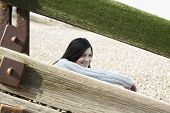Happy young woman looking away while sitting behind balustrade at beach