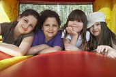 Portret van gelukkige jonge meisjes ontspannen in springkasteel