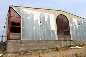 Exterior of rundown commercial building with sky background.