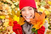 Autumn woman holding fall leaves in forest smiling happy and excited. Cute close up portrait of girl