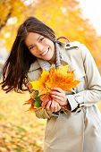 Fall / Autumn woman holding colorful leaves in city park smiling happy. Stylish modern portrait of g