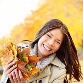 Autumn / Fall woman holding colorful leaves in city park smiling happy. Stylish modern portrait of girl showing colorful leaves outdoor in fall forest foliage. Mixed race Asian Caucasian female model.
