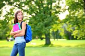 Back to school student girl looking to side in park holding books and note books wearing backpack. Female university college student looking at copyspace in park. Beautiful young multiracial woman.