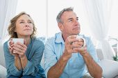 Thoughtful middle aged couple sitting on the couch having coffee looking away at home in the living