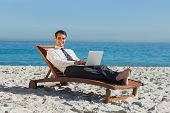 Smiling young businessman on the beach lying on a deck chair with his laptop