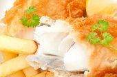 picture of hake  - Close up of a broken piece of fried fish with chips - JPG