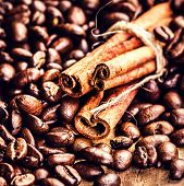 Macro Coffee Beans And Cinnamon Sticks On Grunge Wooden Background. Fresh Roasted Coffee Beans On Vi