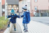 Two Little Sibling Boys Walking On The Street In German Village.