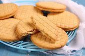 Sandwich Biscuits With Syrup Filling On Blue Wooden Background