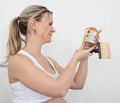 Pregnant Renovating With Paint Can And Brush