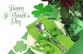stock photo of leprechaun hat  - Happy St Patricks Day table setting with shamrocks and leprechaun hat and sample text greeting on green and white background - JPG