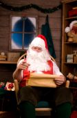 Santa Claus In Rocking Chair With Naughty Pointing At Camera