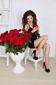 Beautiful Fashion Brunette Girl With Bouquet Of Red Roses. Valentine's Day. Happy Sexy Brunette Woma
