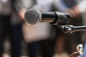 foto of politician  - Microphone on the background blurred figures of people during a rally closeup - JPG