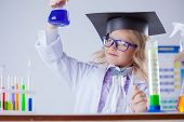 Smart girl looking at color of reagent in flask