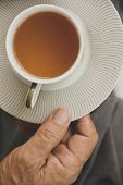 a hand ilfts a cup of tea
