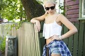 Blonde teenage girl model in front of wooden house