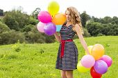 beautiful young blonde girl smiles on a summer day walks with colored balls in the city