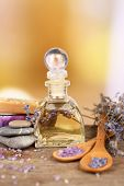 Spa still life with lavender oil and flowers on wooden table, on light background