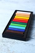 Colorful chalk pastels in box on wooden background
