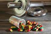 Dumbbell and colorful pills, tablets, on wooden background