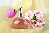 Perfume bottle with roses on fabric background