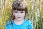 Little girl in blue dress with polka dots in tall grass