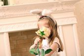 Little Beautiful Girl In White Dress And Bunny Ears Sniffs Big White Rose