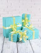 Beautiful gifts on table on brick wall background