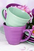 Bright cups and saucers with flowers on table on bright background