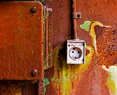 Old Electrical Outlet On The Rusty Iron Wall