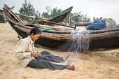 HOI AN, VIETNAM - APRIL 3, 2014: Unidentified fishermen repairing fishing nets on the beach near Hoi