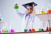 stock photo of reagent  - Young chemist posing with variety of reagents in lab - JPG