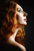 Closeup Studio Portrait Of Beautiful Redhead Woman. Profile View