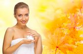 Healthy girl with body cream on autumn background