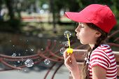 Cute girl blowing soap bubbles