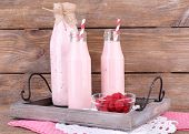 Bottles of raspberry smoothie drink on wooden background