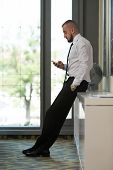Business Man Texting On Cellphone In Modern Office