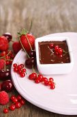 Ripe sweet berries and liquid chocolate on wooden table